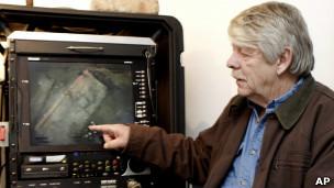 Грег Брукс показывает кадры подводной видеосъемки, на которых видны металлические слитки